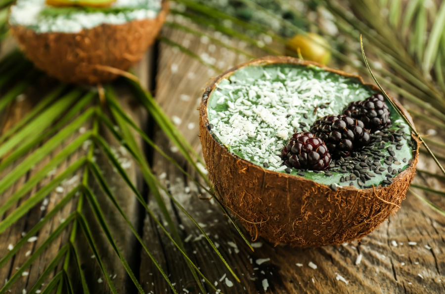 Tropical Coconut Bowl Full Of Healthy Green Smoothie Made With Coconut Water With Pulp Topped With Shredded Coconut Blackberries And Seeds