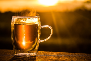 Golden Cup Of Hot And Fresh Steeped Tea In Clear Mug Outside In Golden Hour Lighting