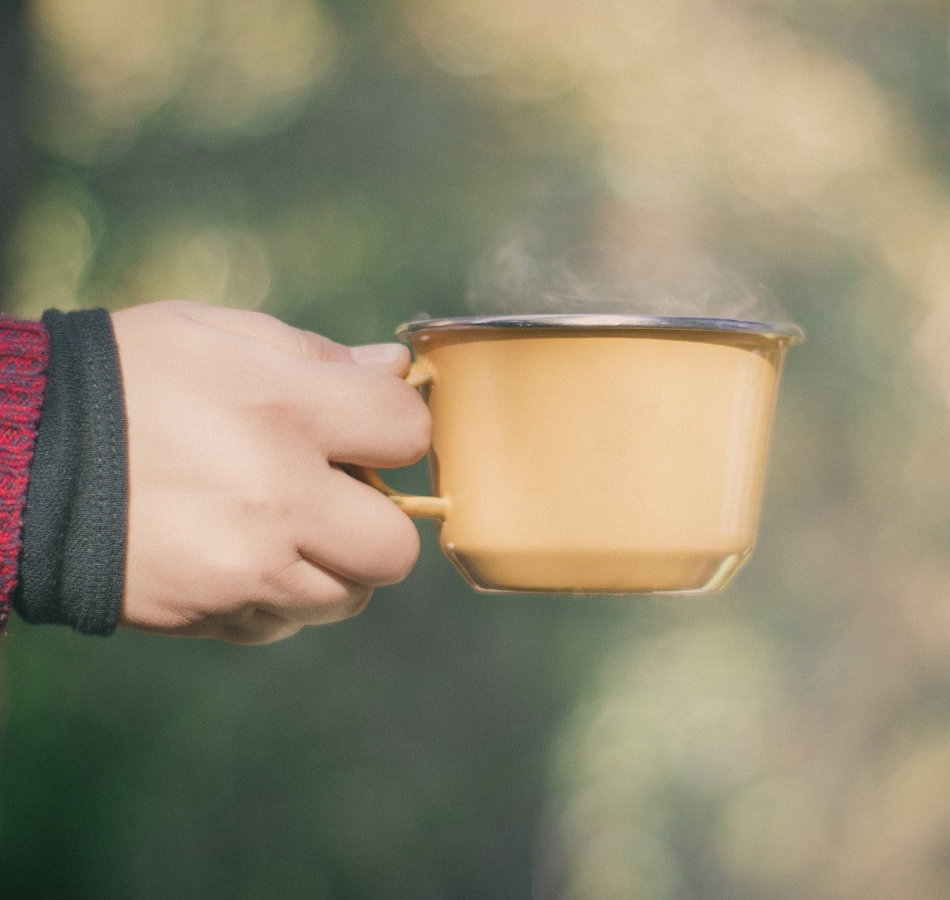 Hand Holding Steaming Hot Yellow Metal Camp Mug Of Organic Colombian Coffee Outdoors