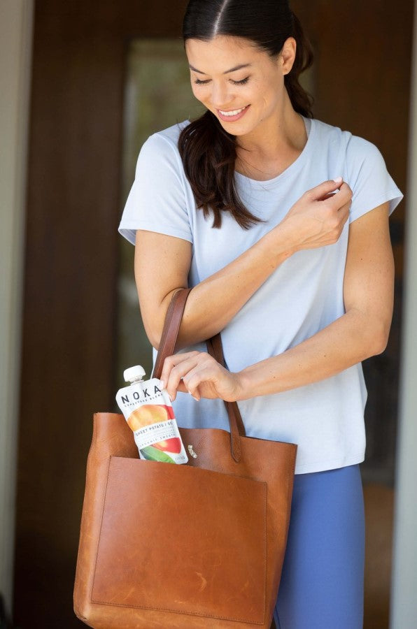 Woman Pulling An Organic Noka Smoothie Pouch Out Of Her Bag For On The Go Healthy Snacking Goji Berry Sweet Potato Flavor