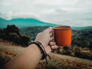 Hand Holding Orange Metal Camp Cup Of Organic Coffee Outdoors