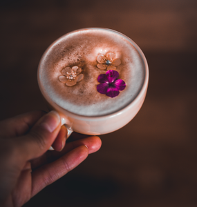 Hand Holding A Cup With Foamy Latte Topped With Three Flowers