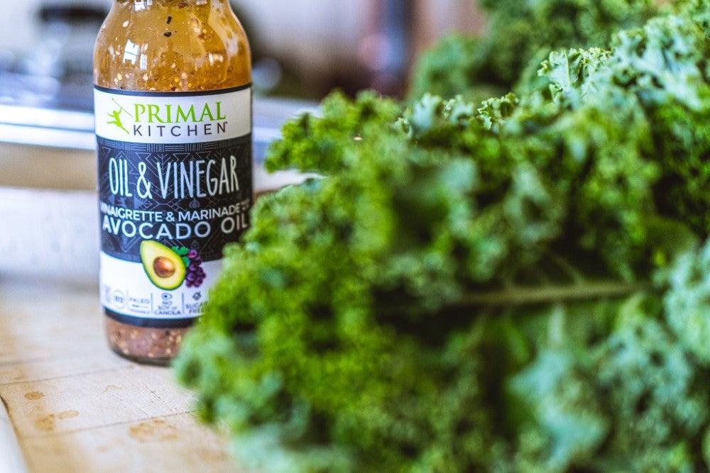Bottle Of Primal Kitchen Oil & Vinegar Vinaigrette & Marinade Made With Avocado Oil Next To Leafy Kale For Keto Kale Salad With Avocado Oil And Vinegar Dressing Primal Kitchen Recipe