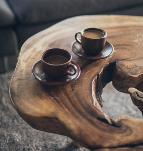 Two Cups And Saucers With Organic Colombian Coffee On Natural Tree Slice Wood Table