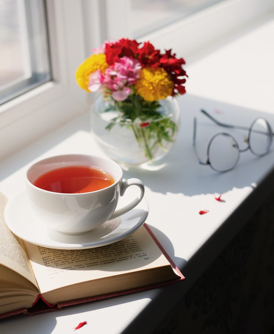 Beautiful Cup Of Tea In Sunlight With Book Glasses And Vase Of Colorful Flowers