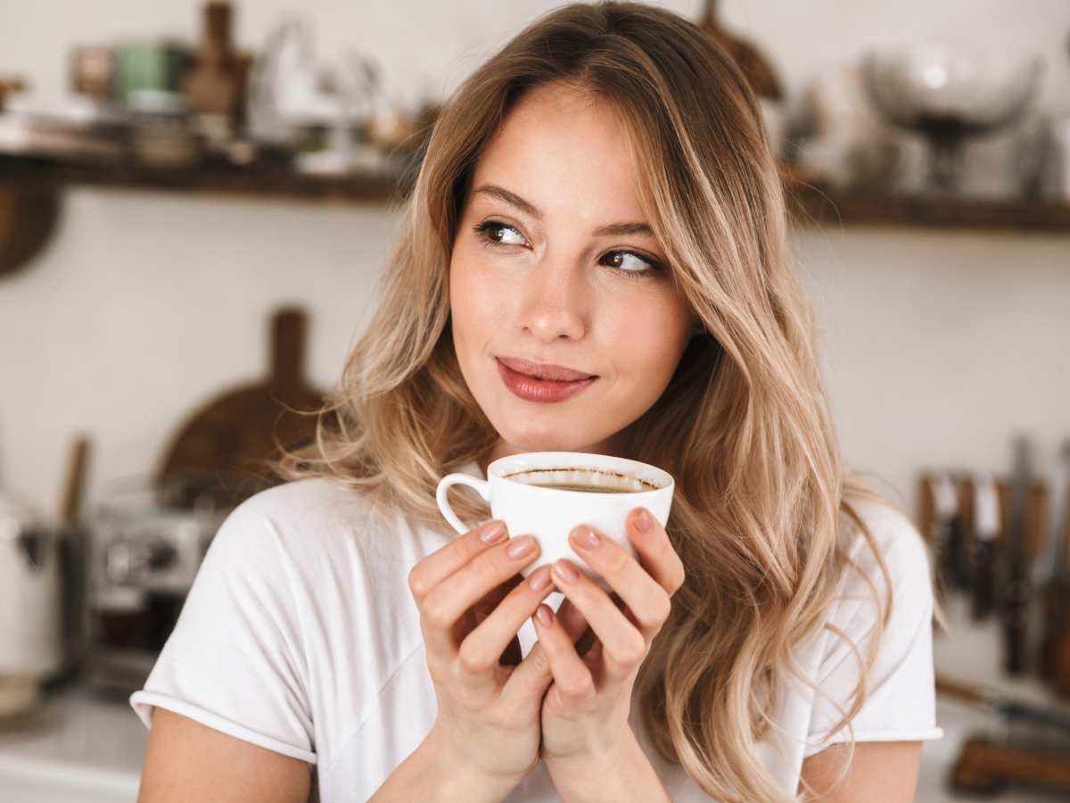 Woman Happily Holding White Cup Of Organic Italian Roast Coffee In Kitchen
