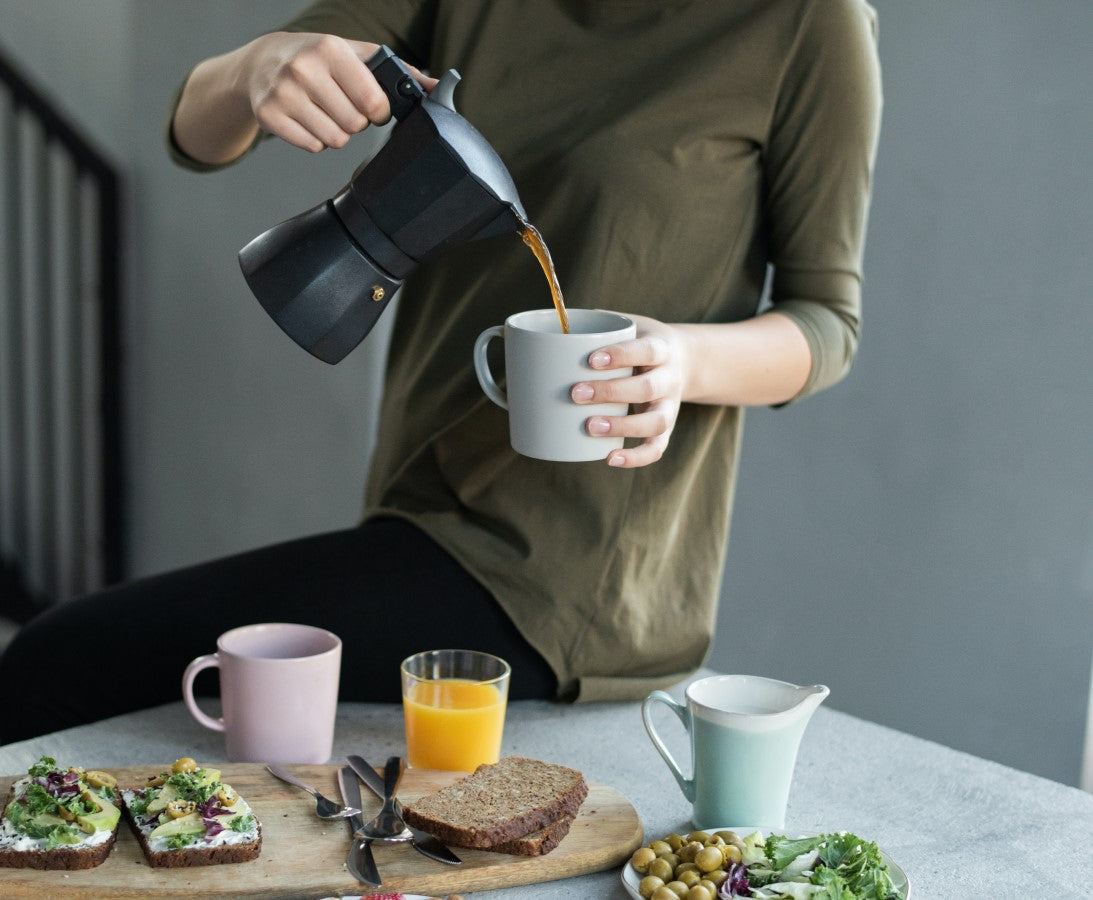 Woman Pouring Colombian Coffee From Moka Pot Into Mug To Go With A Healthy Breakfast
