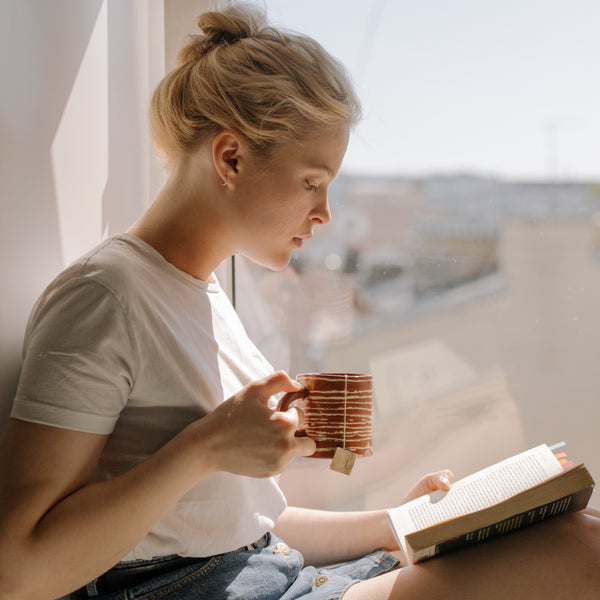 girl reading a book while she's drinking a cup of Tearapy BoosTea tea