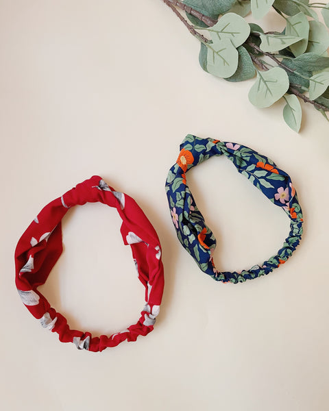 One red knotted headband and one navy blue floral knotted headband laying next to each other.