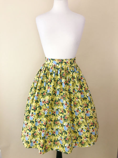 A yellow floral skirt on a mannequin.