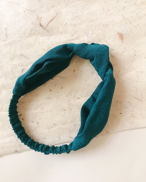 Knotted dark green headband against an off white background.