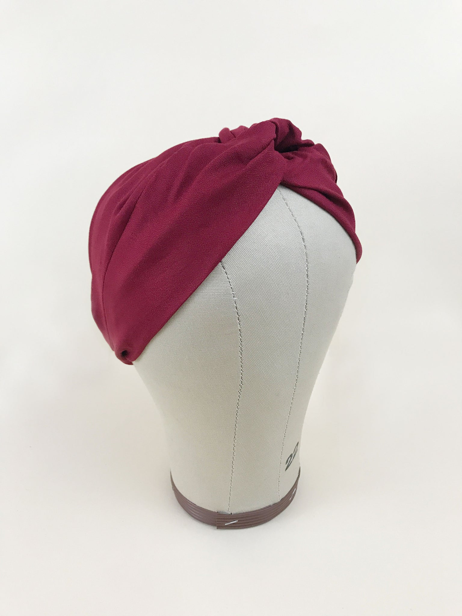 A red twisted headband on a mannequin head.