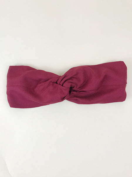 A red twisted headband laying flat on an off-white background.