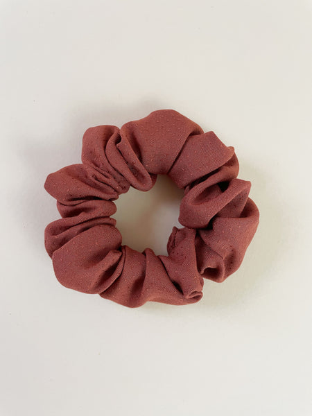 A rust-colored scrunchie laying on an off-white surface.