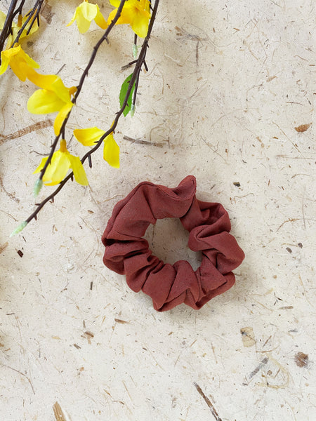 A rust-colored scrunchie laying next to yellow flowers.