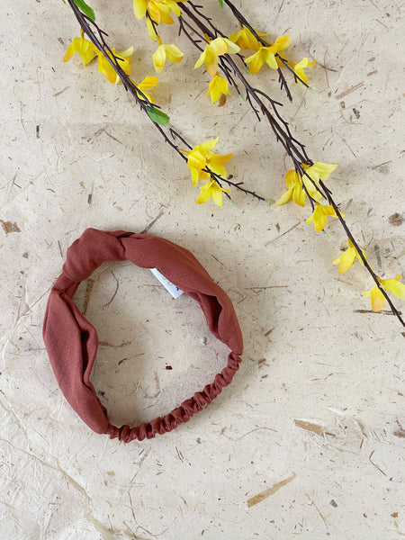 A rust-colored knotted headband laying next to yellow flowers.