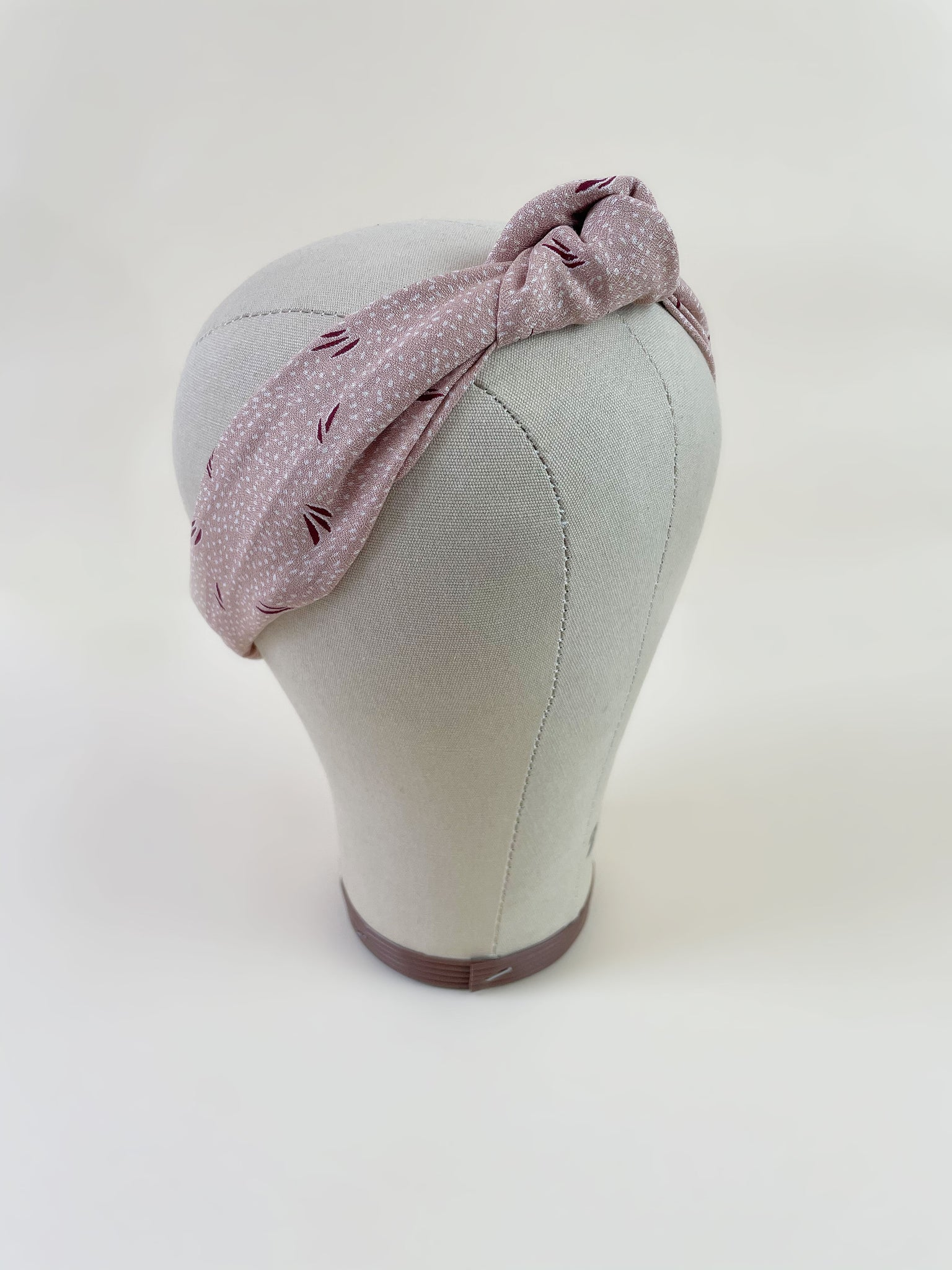 A light pink knotted headband with a dotted and grass print on a mannequin head.