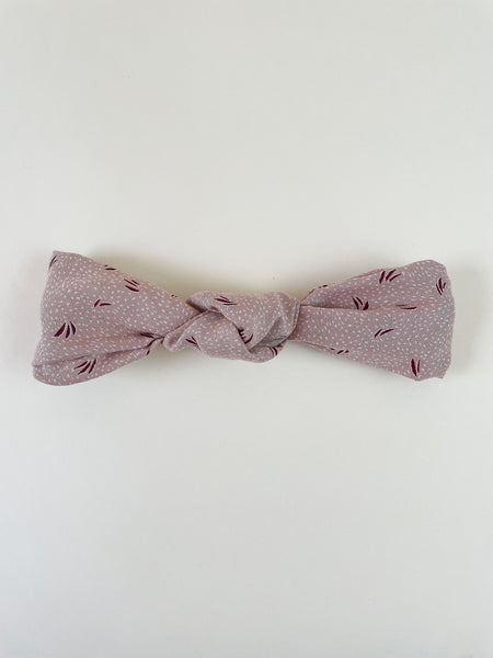 A light pink knotted headband with a dotted and grass print laying on an off-white surface.
