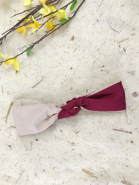 A red and pink knotted headband laying next to yellow flowers.