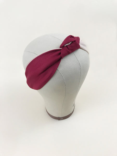 A red and pink knotted headband worn by a mannequin head.