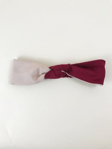 A red and pink knotted headband laying on an off white surface.