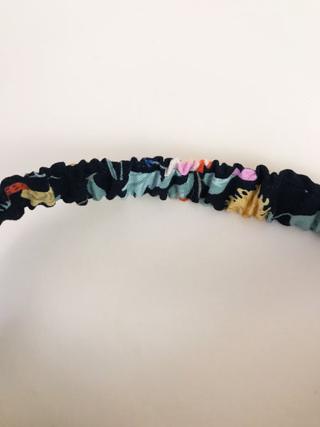 A vibrant floral headband with an elastic band.