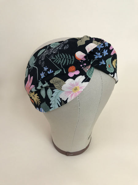 A vibrant floral headband on a mannequin head.