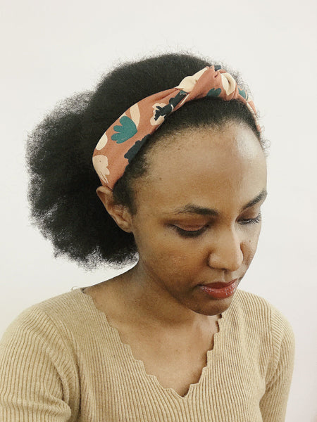 A brown knotted headband with flowers modeled by an African American woman with afro hair.