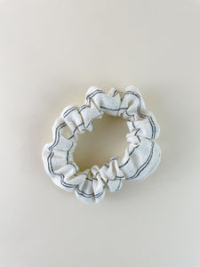 An ivory scrunchie with black stripes on an off white surface.