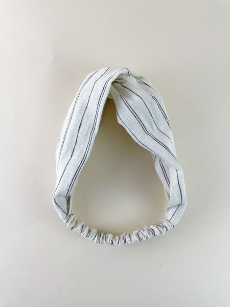 An ivory twisted headband with black stripes on an off white surface.