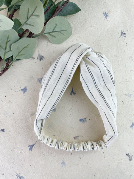 An ivory twisted headband with black stripes next to eucalyptus leaves.