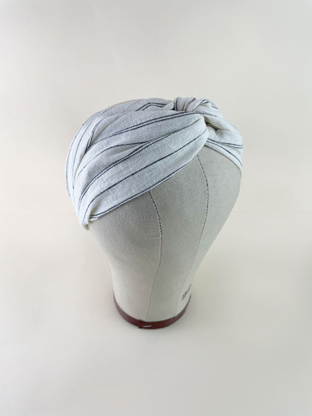 An ivory twisted headband with black stripes on a mannequin head.