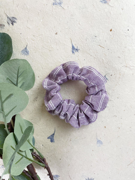A lavender scrunchie with ivory stripes next to eucalyptus leaves.