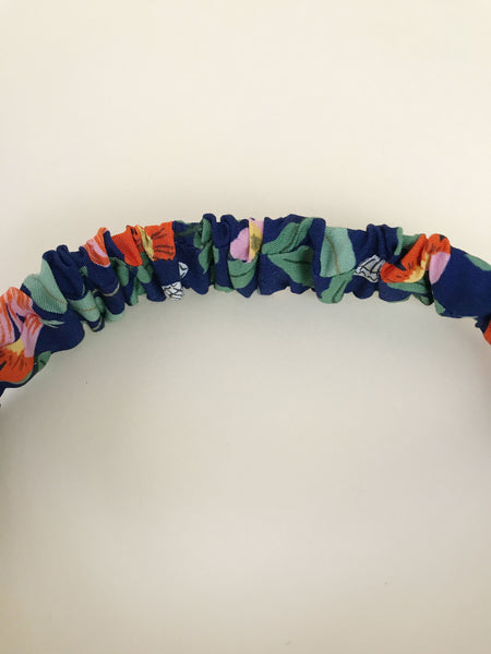 A navy blue floral twisted headband with elastic band.