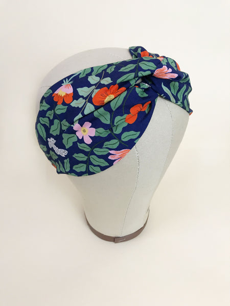 A navy blue floral twisted headband on a mannequin head.