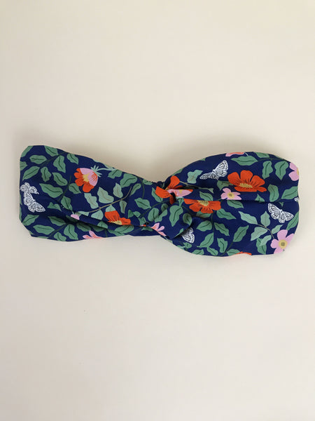 A navy blue floral twisted headband.