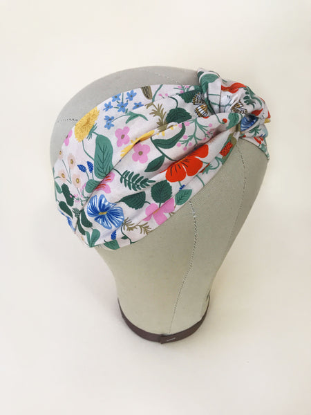A pink twisted headband with a vibrant floral print modeled on a mannequin head.
