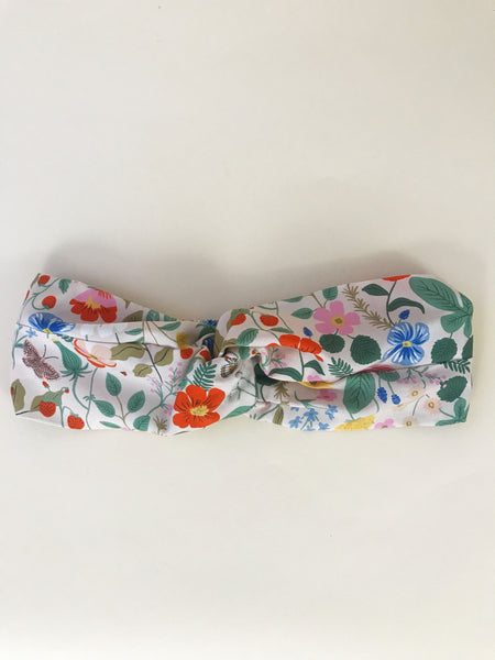 A pink twisted headband with a vibrant floral print laying on an off white surface.