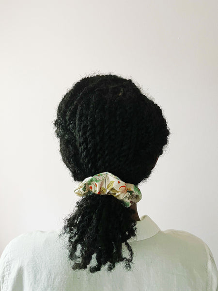 A blush pink scrunchie worn by an African American woman with her twisted hair in a low ponytail. The scrunchie has vibrant flowers with ladybugs and white butterflies.