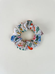 A blush pink scrunchie on an off-white surface. The scrunchie has vibrant flowers with ladybugs and white butterflies.