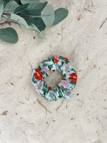 A mint green scrunchie next to eucalyptus leaves. The scrunchie has red and pink flowers with green leaves and white butterflies.