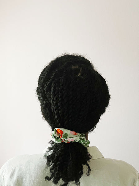 A mint green scrunchie worn by an African American woman with her twisted hair in a low ponytail. The scrunchie has red and pink flowers with green leaves and white butterflies.