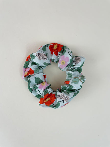 A mint green scrunchie on an off-white surface. The scrunchie has red and pink flowers with green leaves and white butterflies.