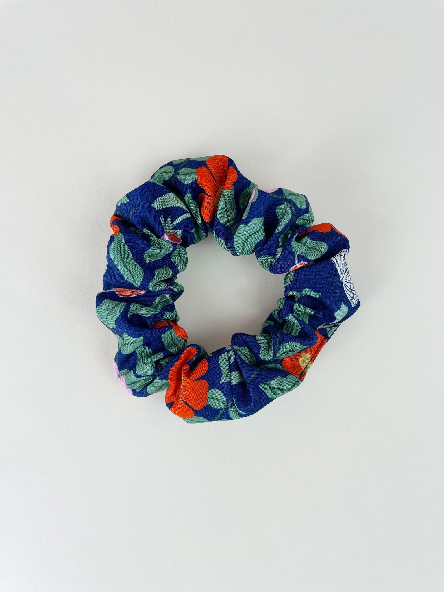 A navy blue scrunchie on an off-white surface. The scrunchie has red and pink flowers with green leaves and white butterflies.