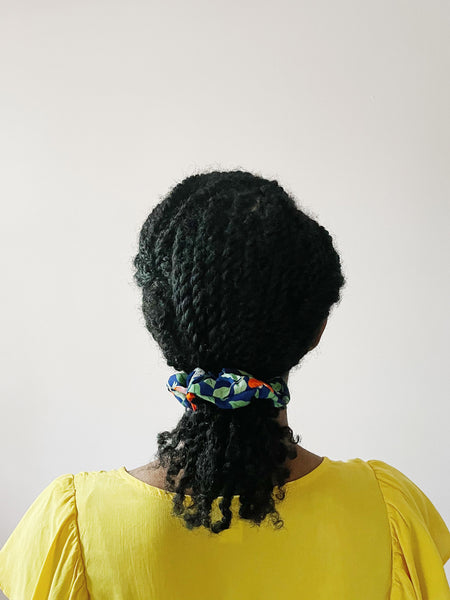 A navy blue scrunchie worn by an African American woman with her twisted hair in a low ponytail. The scrunchie has red and pink flowers with green leaves and white butterflies.