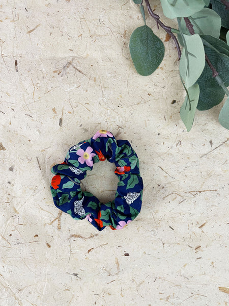 A navy blue scrunchie next to eucalyptus leaves. The scrunchie has red and pink flowers with green leaves and white butterflies.