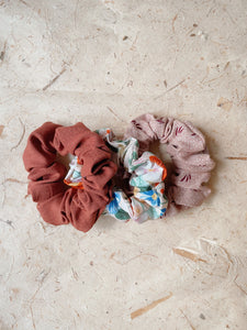 A trio of boho scrunchies on a textured background. The first scrunchie is rust-colored. The second scrunchie is floral with a blush pink background. The third scrunchie is blush pink with cream dots and a dark burgundy grass print.