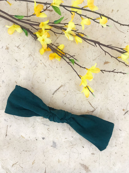 Knotted dark green headband next to yellow flowers.