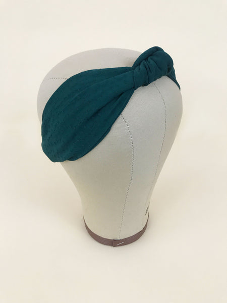 Knotted dark green headband on a mannequin head.