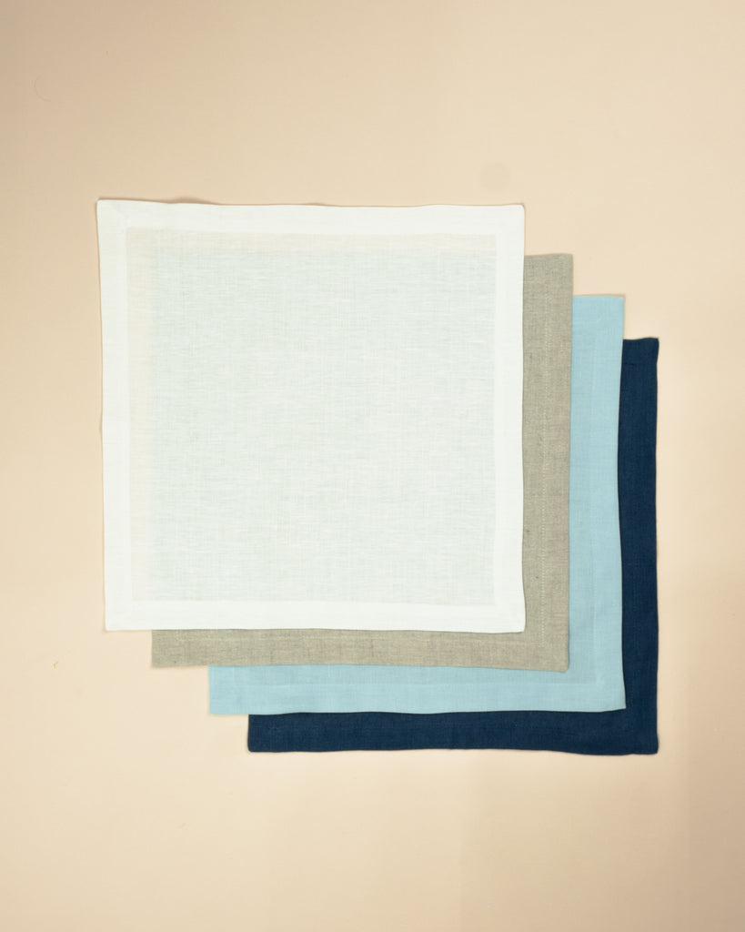 Set of four plain colour napkins, one white, one beige, one light blue, one dark blue